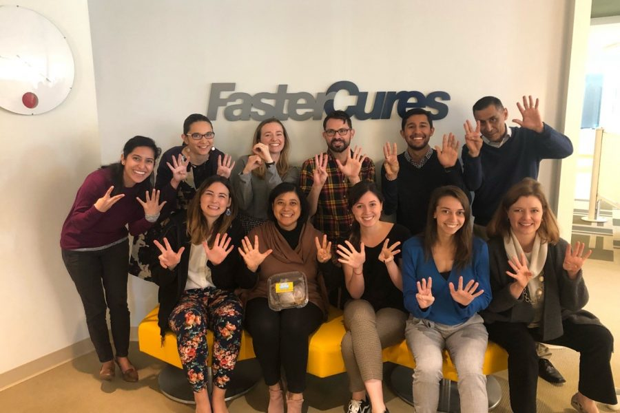 Julien Rashid and coworkers pose in front of Faster Cures sign